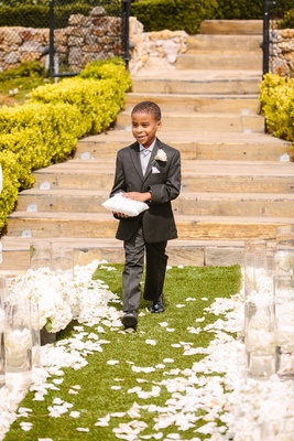 ring bearer in dark grey suit smiles while walking down aisle with ring pillow