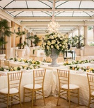 bellagio las vegas wedding reception four long tables form an x with flower arrangement in middle
