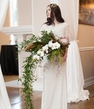 a bride with a headpiece stands with a large cascading bouquet of white flowers and foliage