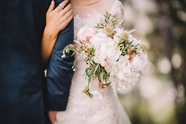 Bride holds groom's arm and carries rustic wedding bouquet