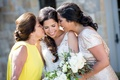 Bride in Monique Lhuillier wedding dress with mother of bride in yellow dress updo and sister