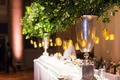 Greenery in silver vase with candle votives at wedding bar