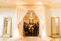 White canopy at reception entrance with seating charts in mirror gold frames on both sides