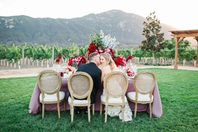 bride and groom kiss at romantic rustic table pink table linens red flowers california vineyard