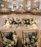 sweetheart table in front of round dance floor, chiavari chairs with blue fabric and florals
