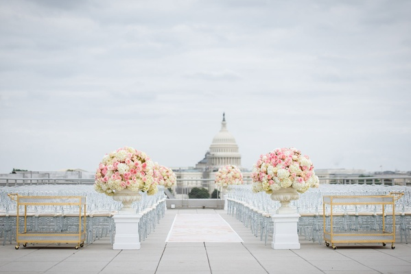 Rooftop wedding ceremony clear guest chairs gold bar carts white pink flowers view of capitol