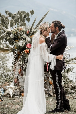 bride in daughters of simone wedding dress kiss groom man bun at boho ceremony lake como
