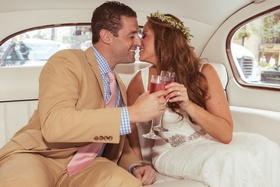 Boho bride and groom toast champagne in classic car