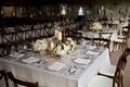 Rustic, elegant wedding reception table with candlestands, white & light pink roses, rustic chairs