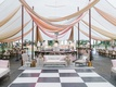 Wedding reception tent checkerboard dance floor lounge furniture wood chairs linen tables bar