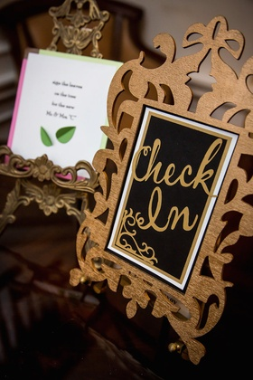 Wedding reception with gold and black check in sign in gilt frame at guest book table