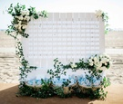 Beachside wedding reception with clapboard place card display, greenery, white roses, flip-flops