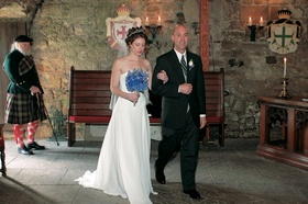 Bride walks down aisle with father in stone castle room