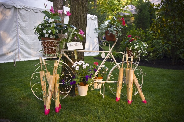 Antique bike sculpture with potted plants and parasols