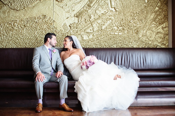 Bride in a strapless fit-and-flare Vera Wang dress sits with groom in grey suit, purple tie