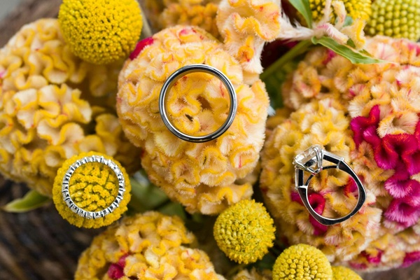 wedding bands and engagement ring on yellow flowers