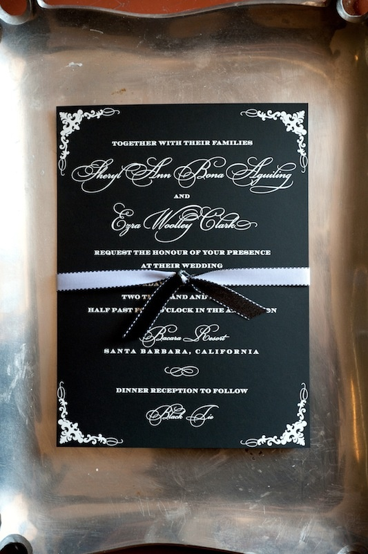 Black wedding invite with white type and ribbon