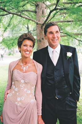 Bride's father and mother in long sleeve gown with corset bodice