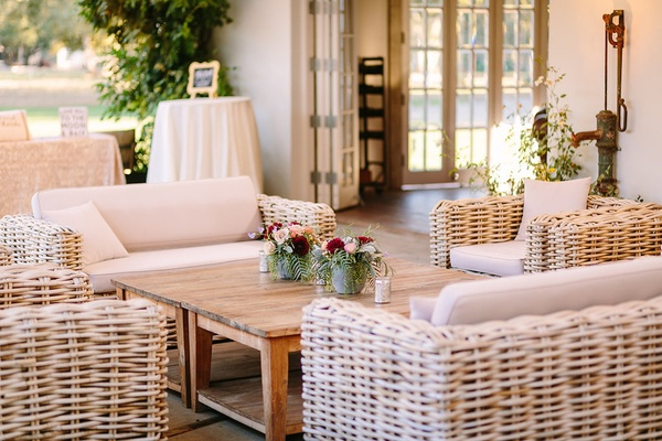 wicker lounge furniture wooden coffee table faux wedding party styled shoot rustic event florals