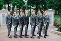 Groom and groomsmen in grey suits, black ties, quirky socks