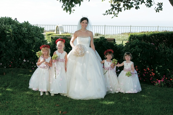 Bride with flower girls in white ball gowns and flower crowns and wands