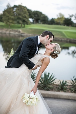 Groom in tuxedo with bow tie kisses bride in champagne Monique Lhuillier wedding dress