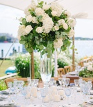 wedding reception centerpiece with ivory roses, hydrangeas, and eucalyptus leaves