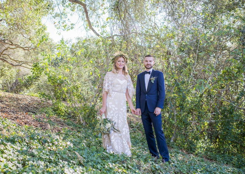 bohemian wedding bride and groom stand in forest on a hillside in santa barbara california