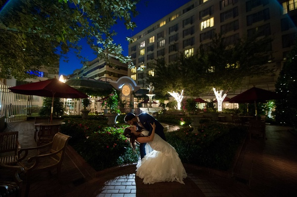 come nightfall, a groom dips his new bride in a courtyard in Washington, DC