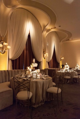 Wedding reception with booth seating velvet banquettes and gold back chairs moody design