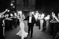 Black and white photo of bride in strapless mermaid dress and groom in tux sparkler exit tunnel