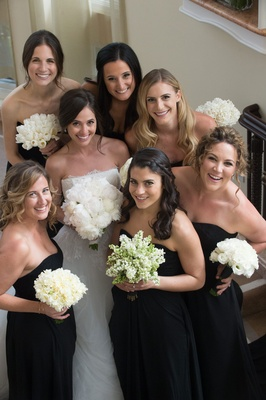 Bride with bridesmaids in black bridesmaid dresses and white bouquets with different flowers