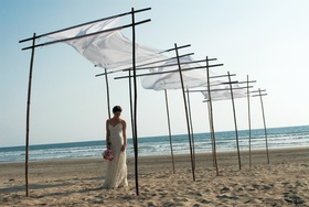 Bride stands on beach under white canopy in Mexico