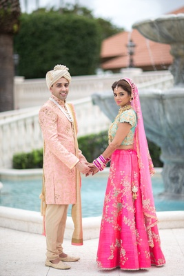 Indian-American bride and groom in traditional wedding attire during first look. lengha, sherwani
