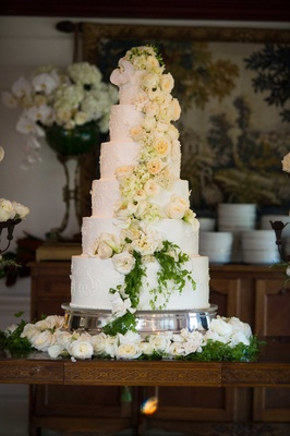 Six tier white wedding cake with fresh cascading rose and orchid flowers