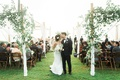 wedding ceremony bride and groom kiss arbor over ceremony seating greenery wood