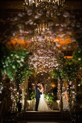 Couple kissing beneath floral altar in ballroom