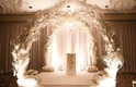 White branch and flower arch for indoor wedding ceremony