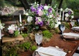 Outdoor wedding reception with wood table, moss runner, urn with white, purple, and green flowers