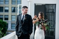 Groom looks to the side as bride taps on his shoulder in inbal dror dress during first look