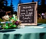 Chalkboard sign for wedding wand at outdoor ceremony