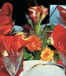 Red tablecloth with red, orange, and yellow flower centerpiece