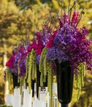 Black vases with purple and green flowers at ceremony