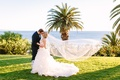 Bride in Demetrios, groom in Ermenegildo Zegna kiss on grass ocean view