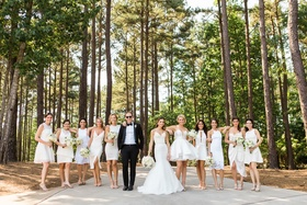 Bridesmaids in mismatched white dresses short with bridesman in tuxedo in woods georgia