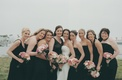 Bride with bridesmaid in black gowns and pink bouquets