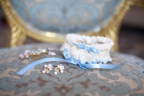 Wedding day garter white lace satin with light blue ribbon on blue chair gold details