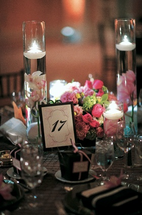 tea lights and flowers float in tall glass vases