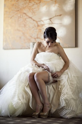 Woman in bridal gown wearing lace garter and heels