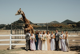 bride with mismatched bridesmaids and bridesmen in front of stanley the giraffe at saddlerock ranch